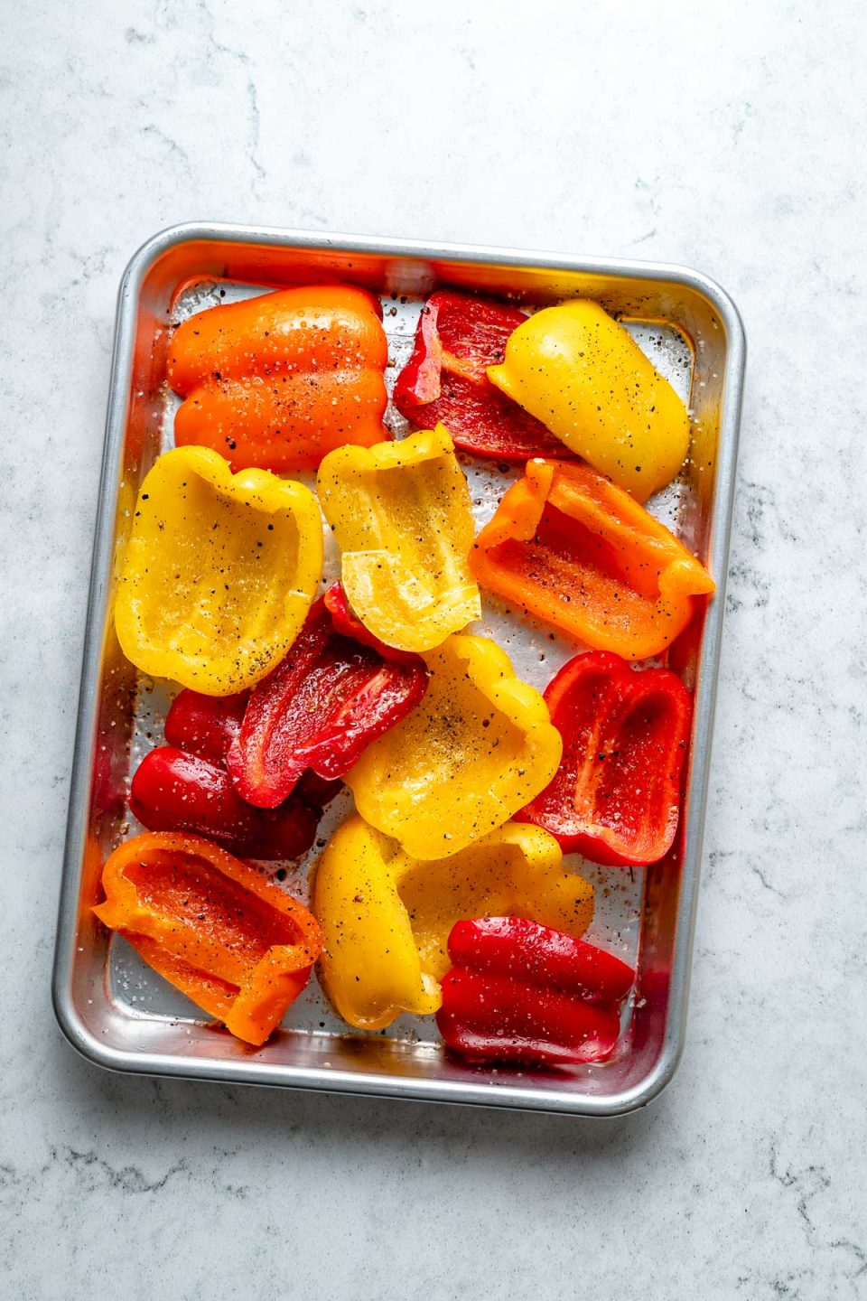 Multiple slices of fresh & raw yellow, orange, & red bell peppers seasoned with avocado oil, kosher salt, & ground black pepper arranged on an aluminum baking sheet. The baking sheet sits on top of a white & gray marble surface.
