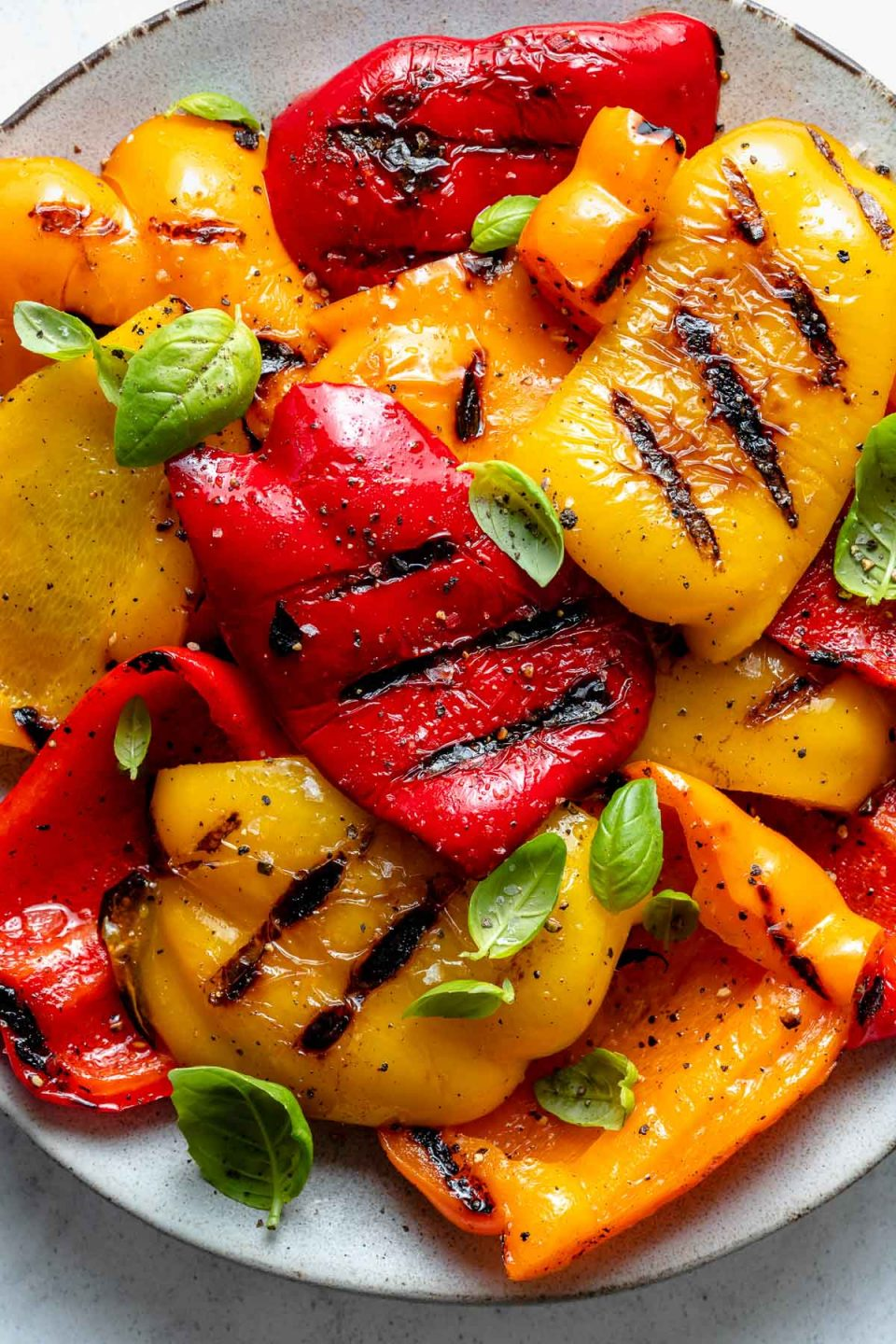 Close up of yellow, orange, & red grilled bell peppers with char marks arranged on a ceramic plate. The grilled bell peppers are garnished with kosher salt, ground black pepper, & fresh herbs. The platter sits on top of a white & gray marble surface.