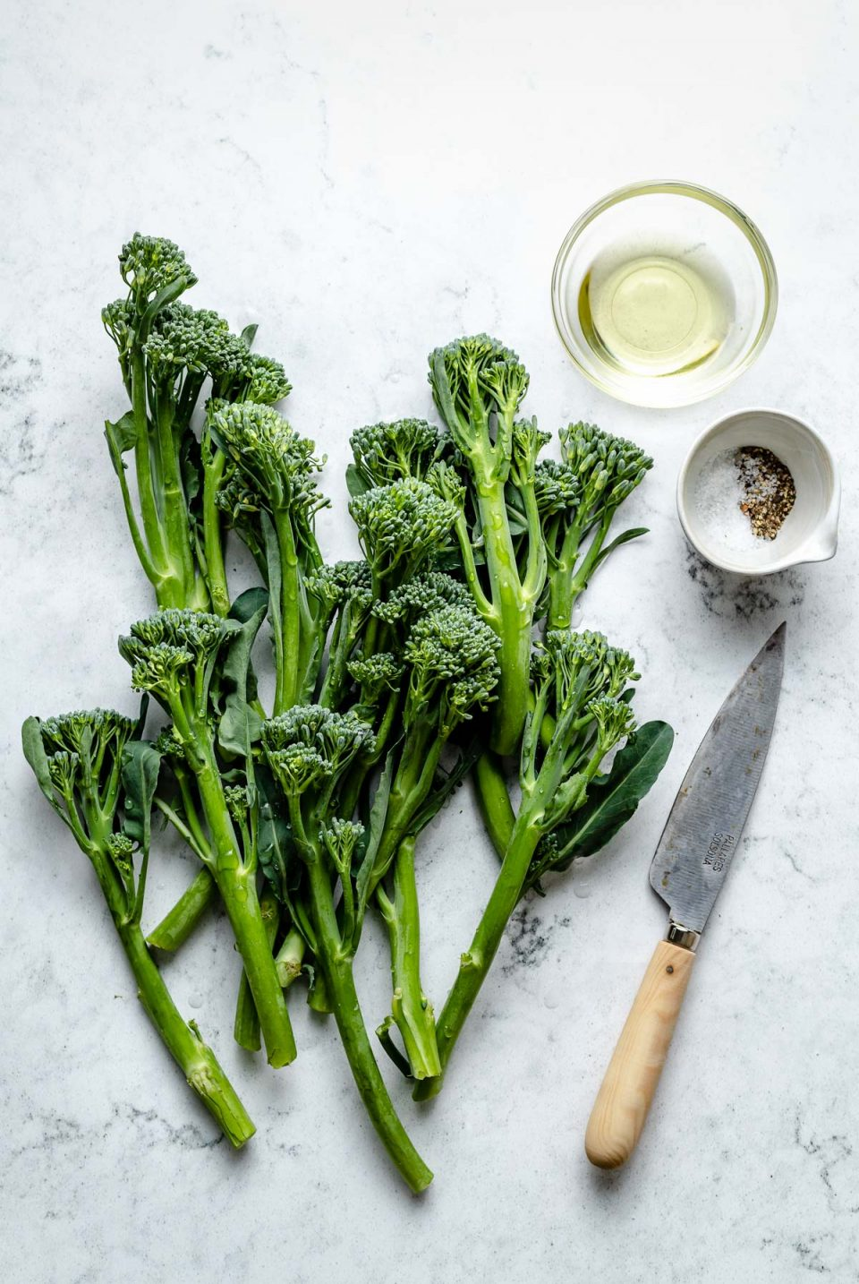 Grilled broccolini ingredients arranged on a white & grey marble surface - broccolini, avocado oil, kosher salt, & ground black pepper. A pairing knife rests on the surface next to the ingredients.
