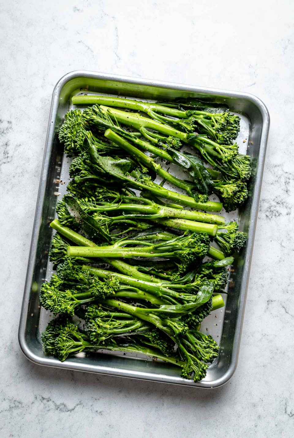 Multiple pieces of fresh & uncooked broccolini stalks seasoned with oil, kosher salt, & ground black pepper lie on an aluminum baking sheet. The baking sheet sits on top of a white & gray marble surface.