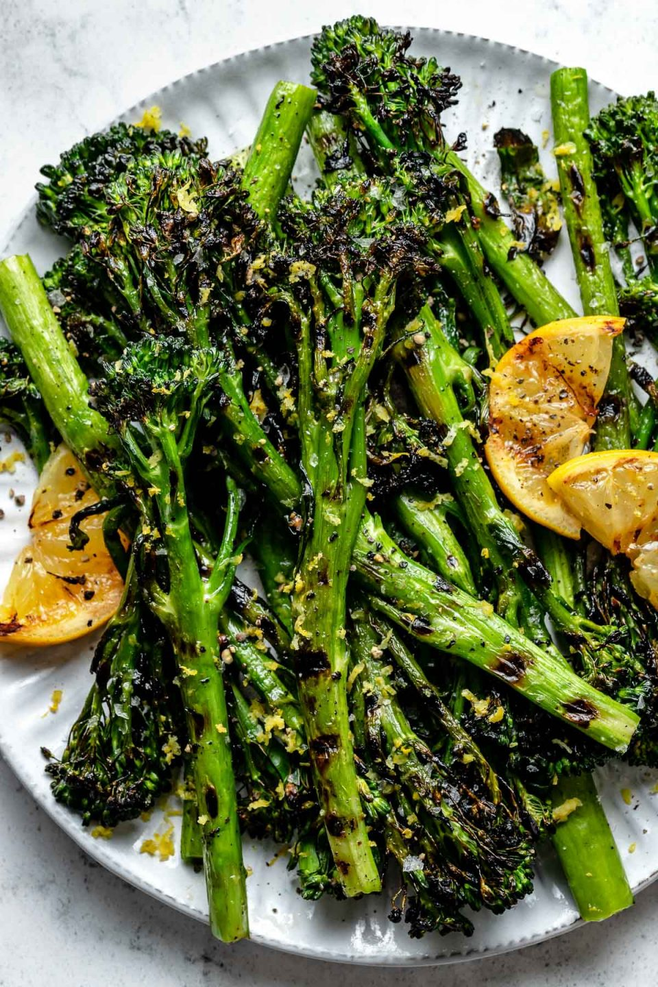 Close up of grilled broccolini with char marks arranged on a white ceramic plate. The pieces of grilled broccolini are garnished with kosher salt, ground black pepper, grilled lemon wedges, & lemon zest. The plate sits on top of a white & gray marble surface.