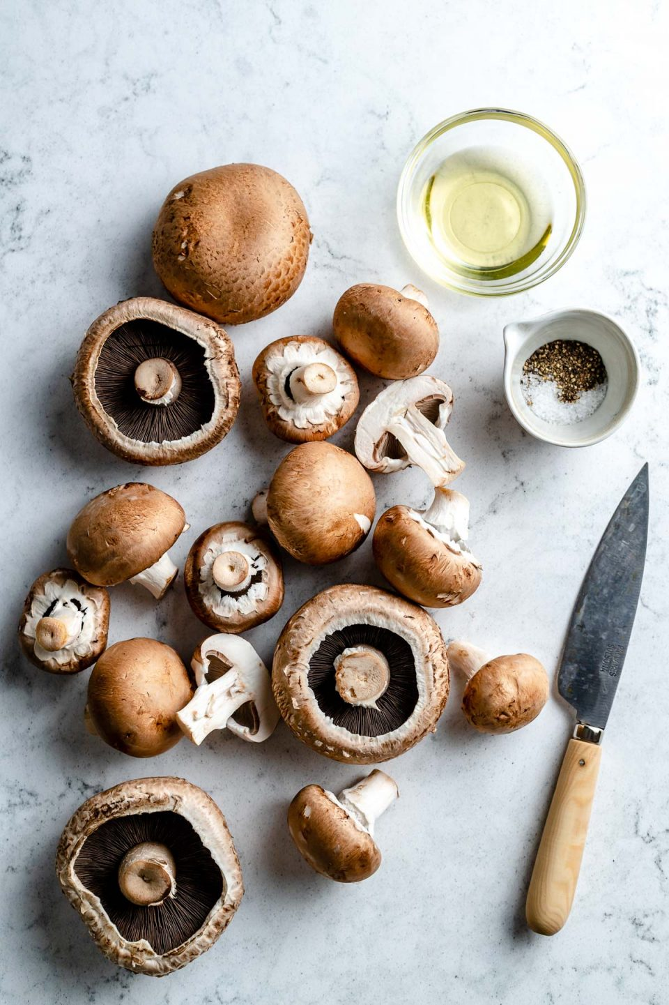 Grilled mushroom ingredients arranged on a white & grey marble surface - whole portobello & cremini mushrooms with a few sliced cremini mushrooms, avocado oil, kosher salt, & ground black pepper. A pairing knife rests on the surface next to the ingredients.