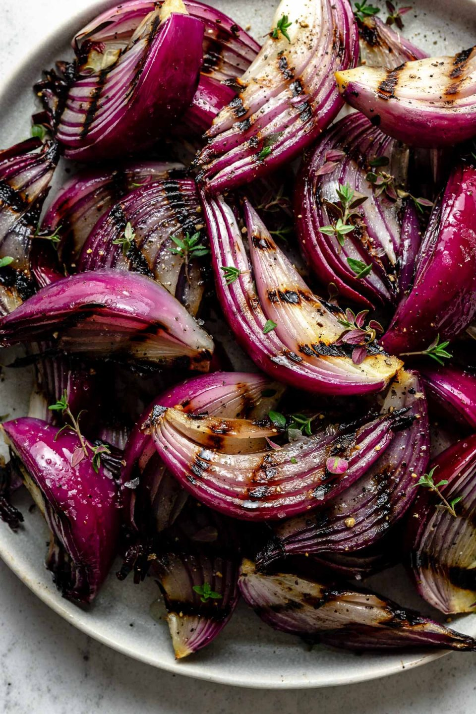 Close up of grilled onion slices with char marks arranged on a white ceramic plate. The grilled red onion slices are garnished with kosher salt, ground black pepper, & fresh herbs. The platter sits on top of a white & gray marble surface.