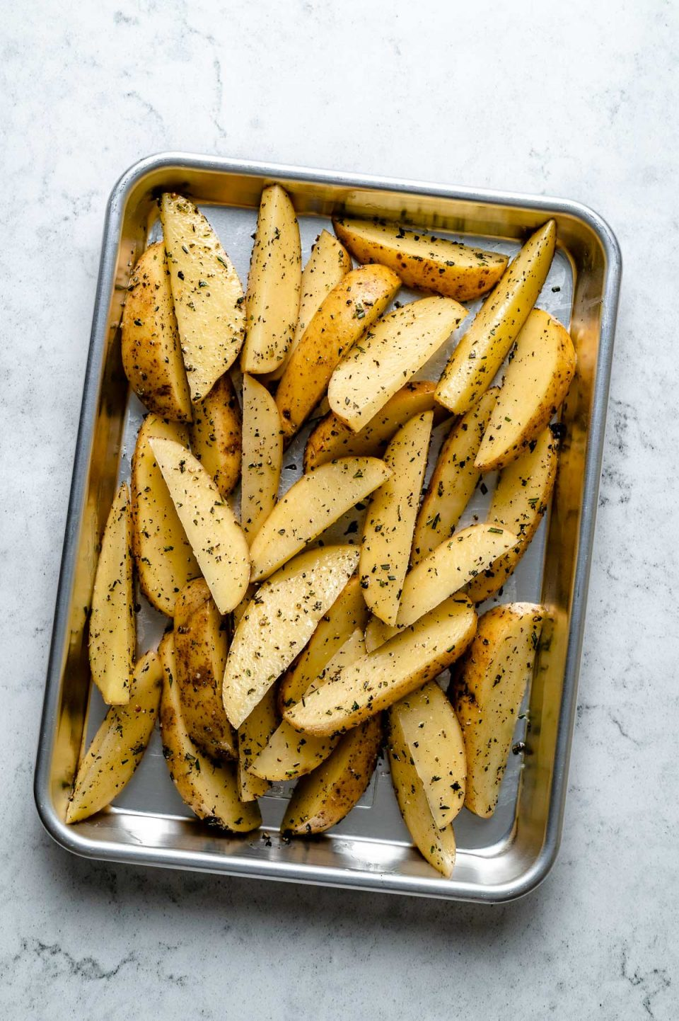 Multiple slices of potato cut in wedges & seasoned with avocado oil, kosher salt, & ground black pepper arranged on an aluminum baking sheet. The baking sheet sits on top of a white & gray marble surface.