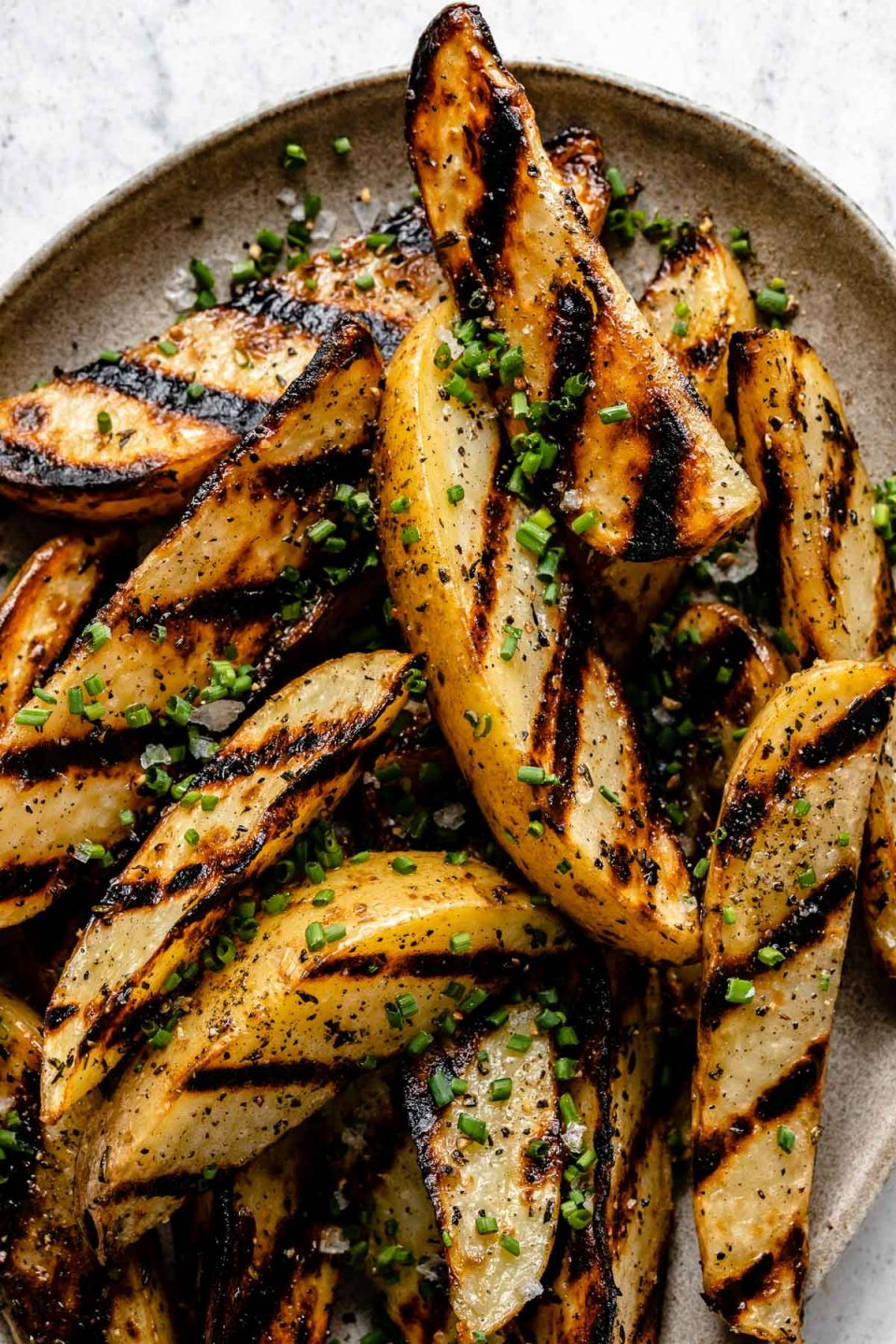 Close up of grilled potato wedges with char marks arranged on a brown speckled ceramic platter. The grilled potato wedges are garnished with kosher salt, ground black pepper, & freshly snipped chives. The platter sits on top of a white & gray marble surface.