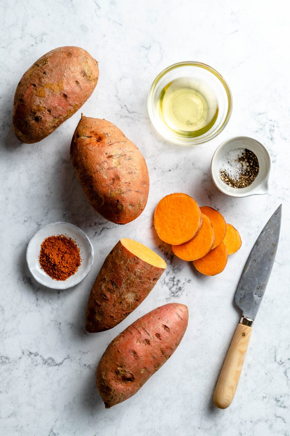 Grilled sweet potato ingredients arranged on a white & grey marble surface - sweet potato, avocado oil, kosher salt, ground black pepper, & optional bbq dry rub. A pairing knife rests on the surface next to the ingredients.