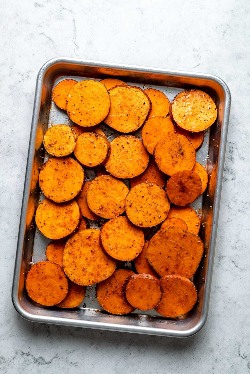 Multiple round slices of fresh & uncooked sweet potato seasoned with avocado oil, kosher salt, & ground black pepper lie on an aluminum baking sheet. The baking sheet sits on top of a white & gray marble surface.