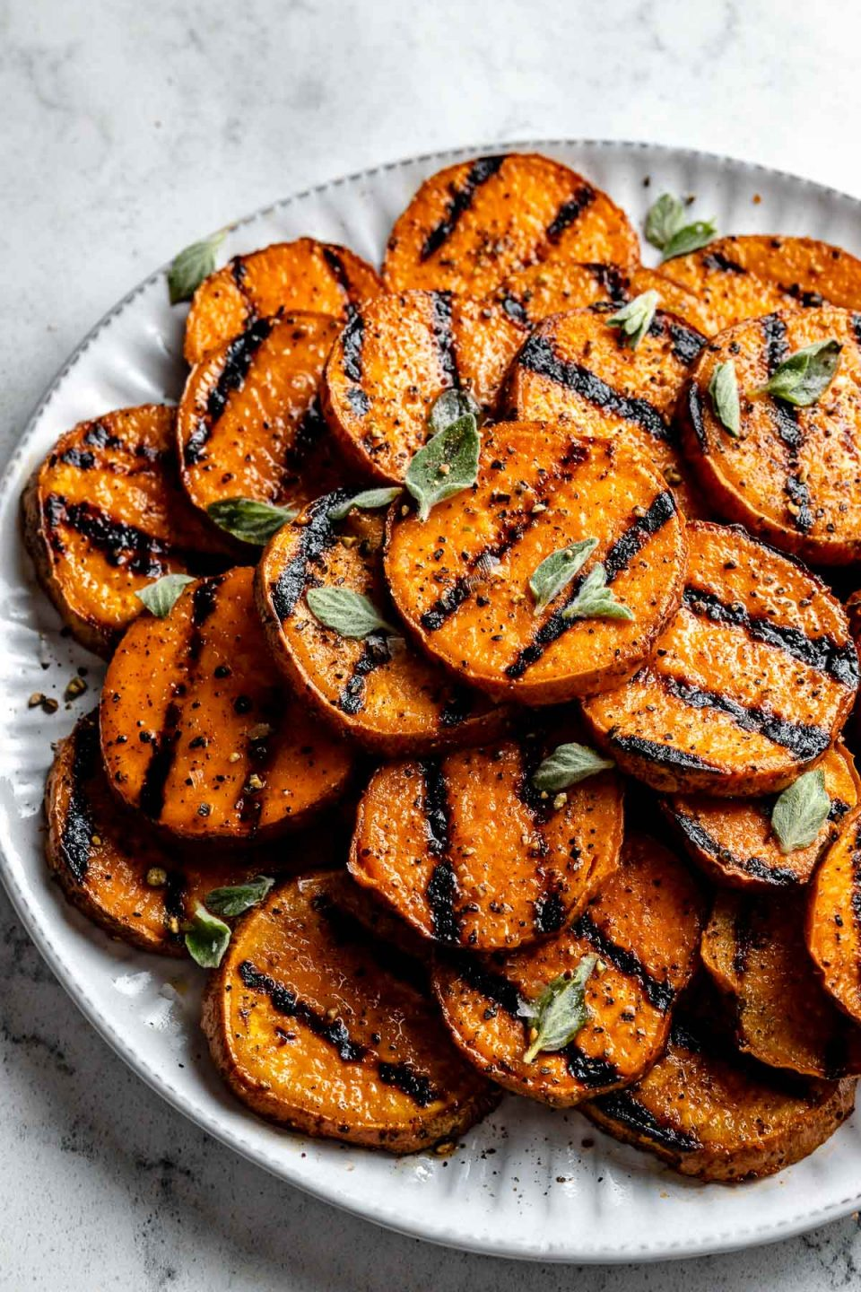 Grilled sweet potato sliced in rounds with char marks are arranged on a white ceramic plate. The sweet potato slices are garnished with ground black pepper, kosher salt, & fresh herbs. The plate sits on top of a white & gray marble surface.