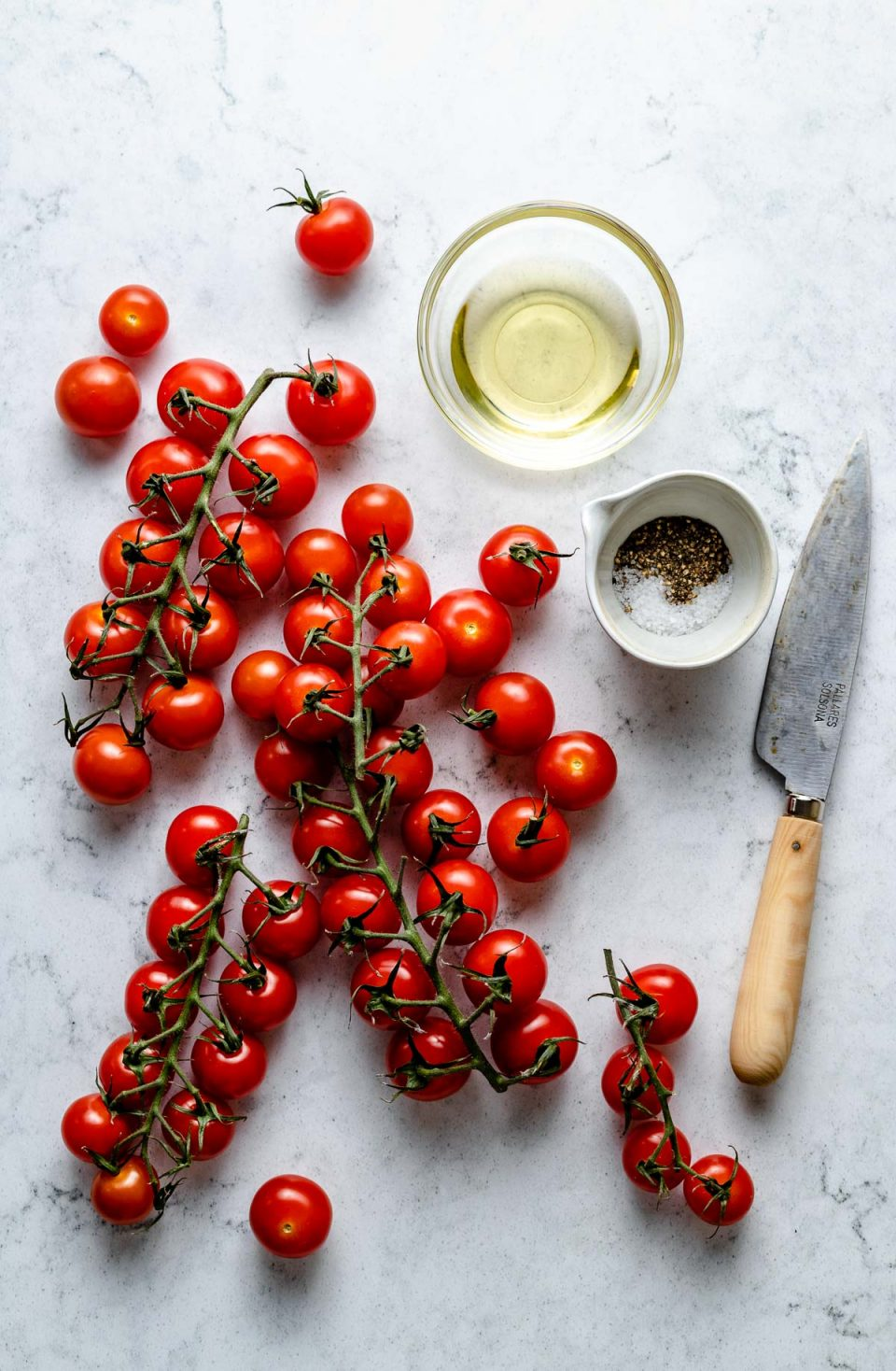 Grilled tomato ingredients arranged on a white & grey marble surface - vines of cherry tomatoes & loose cherry tomatoes, avocado oil, kosher salt, & ground black pepper. A pairing knife rests on the surface next to the ingredients.