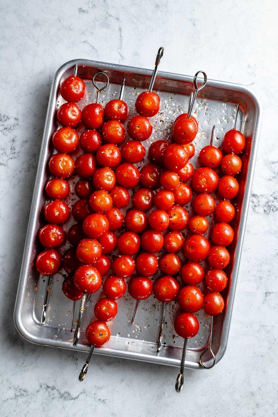 Multiple skewers of fresh & uncooked cherry tomatoes seasoned with oil, kosher salt, and ground black pepper are arranged on an aluminum baking sheet. The baking sheet sits on top of a white & gray marble surface.