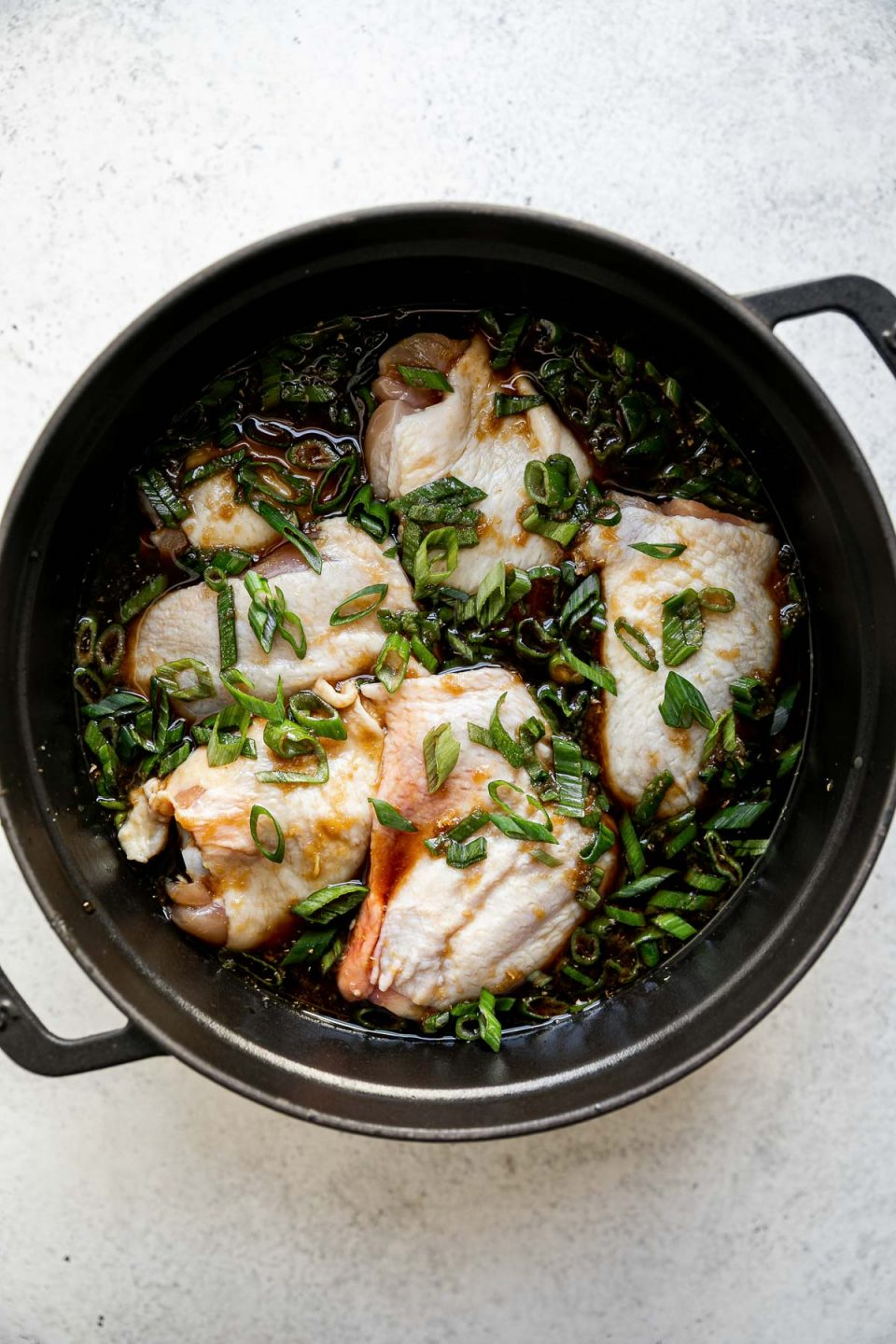 Shoyu chicken assembled in a black dutch oven before braising. The dutch oven sits atop a white surface.