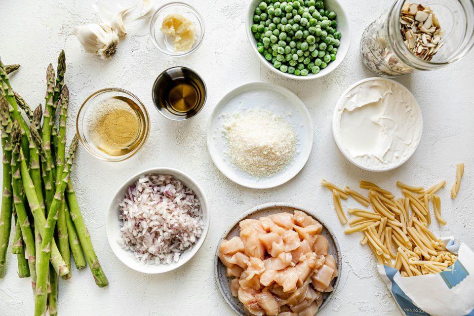 Chicken asparagus pasta ingredients arranged on a white surface: asparagus, garlic, olive oil, white balsamic, shallot, parmesan, mascarpone cheese, frozen peas, diced chicken, sliced almonds, & casarecce pasta