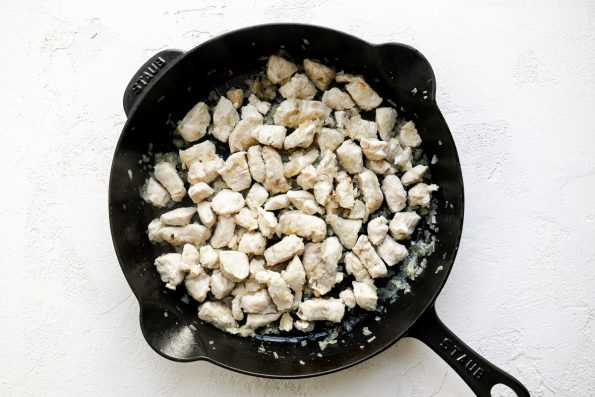 How to make mascarpone pasta sauce, Step 1: browned diced chicken breast & softened shallots in a black cast iron skillet, sitting atop a white surface.