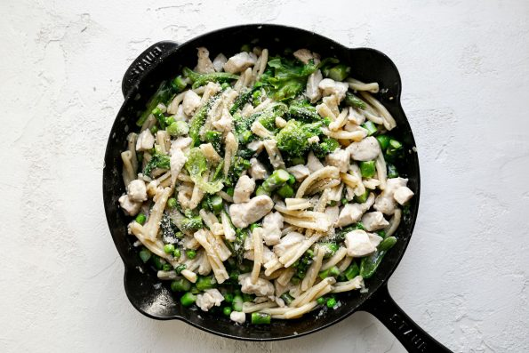 Chicken asparagus pasta in a large black cast iron skillet, atop a white surface.
