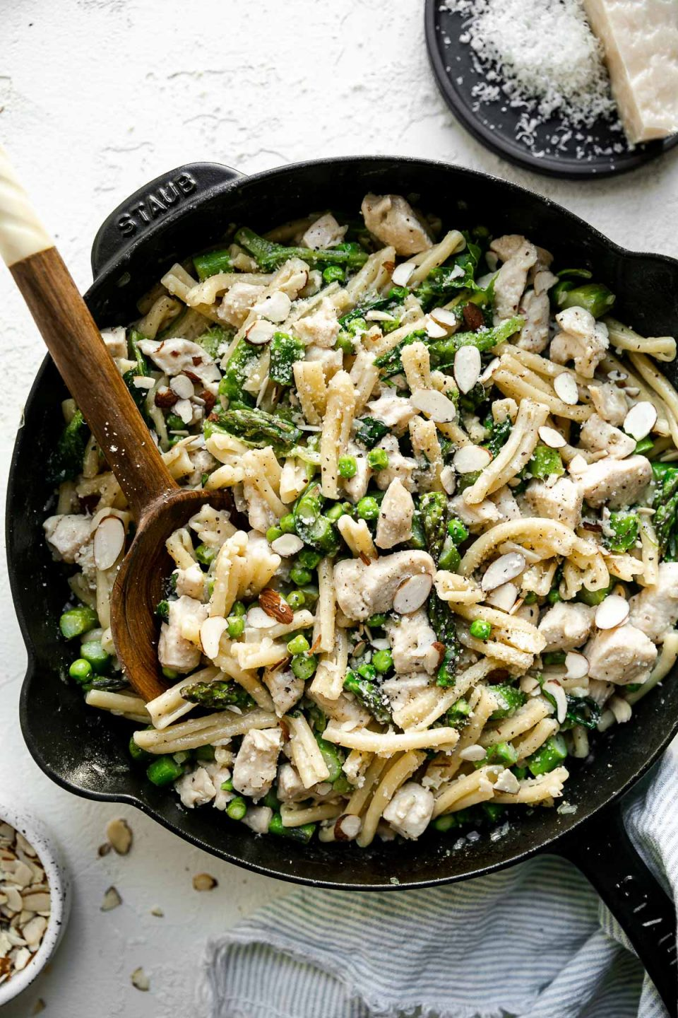 Chicken asparagus pasta in a large black cast iron skillet, atop a white surface. There is a wooden serving spoon nestled in the pasta. The skillet is surrounded by a blue & white striped linen napkin, a small dish of sliced almonds, & a plate with grated parmesan.