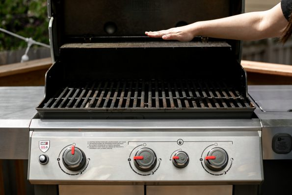 A woman's hand shown above an open Weber Genesis II, prepared for indirect heat grilling with one side of burners all the way open and the other side shut.