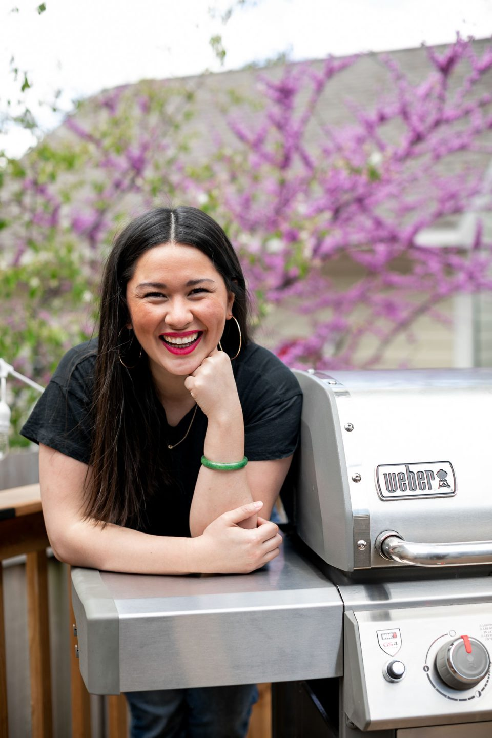 Jess of Plays Well With Butter stands on a deck behind a stainless steel Weber Genesis II propane grill. In the background, a blossoming tree & a house with beige siding.