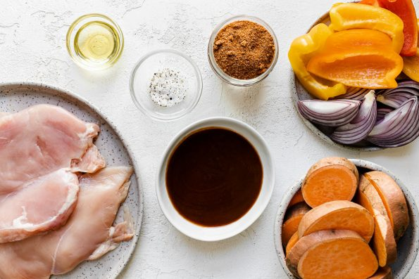 BBQ chicken bowl ingredients arranged on a white surface: thin pounded chicken breasts, oil, BBQ dry rub, BBQ sauce, sliced sweet potatoes, bell peppers & onions.