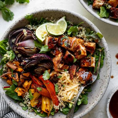Grilled BBQ chicken bowl with diced BBQ chicken, grilled onions, sweet potatoes & bell peppers sitting atop a bed of greens & quinoa in a large speckled gray bowl. The bowl sits atop a white surface, surrounded by a striped gray linen napkin, a second BBQ chicken rice bowl, extra BBQ sauce, cilantro leaves & lime wedges.