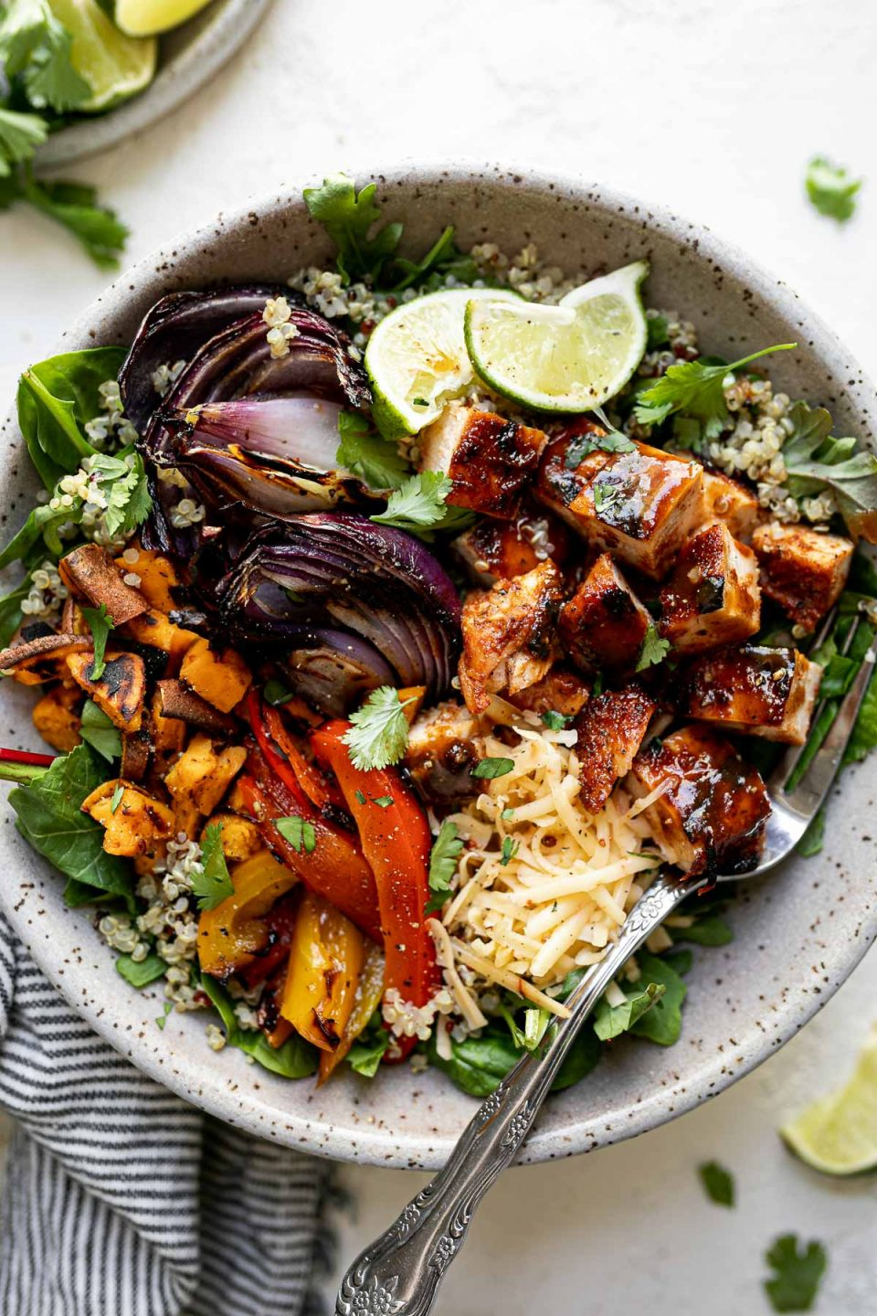 Grilled BBQ chicken bowl with diced BBQ chicken, grilled onions, sweet potatoes & bell peppers sitting atop a bed of greens & quinoa in a large speckled gray bowl. The bowl sits atop a white surface, surrounded by a striped gray linen napkin, cilantro leaves & lime wedges.