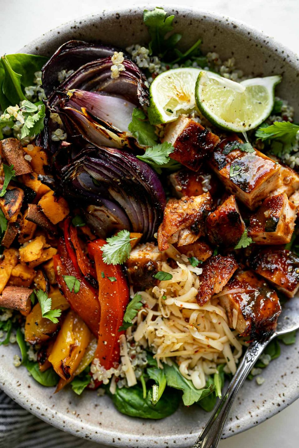 Close up of grilled BBQ chicken bowl with diced BBQ chicken, grilled onions, sweet potatoes & bell peppers sitting atop a bed of greens & quinoa in a large speckled gray bowl. The bowl sits atop a white surface.