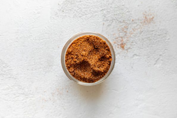 How to make BBQ Chicken Bowls, Step 2: BBQ dry rub in a small jar, sitting atop a white surface.