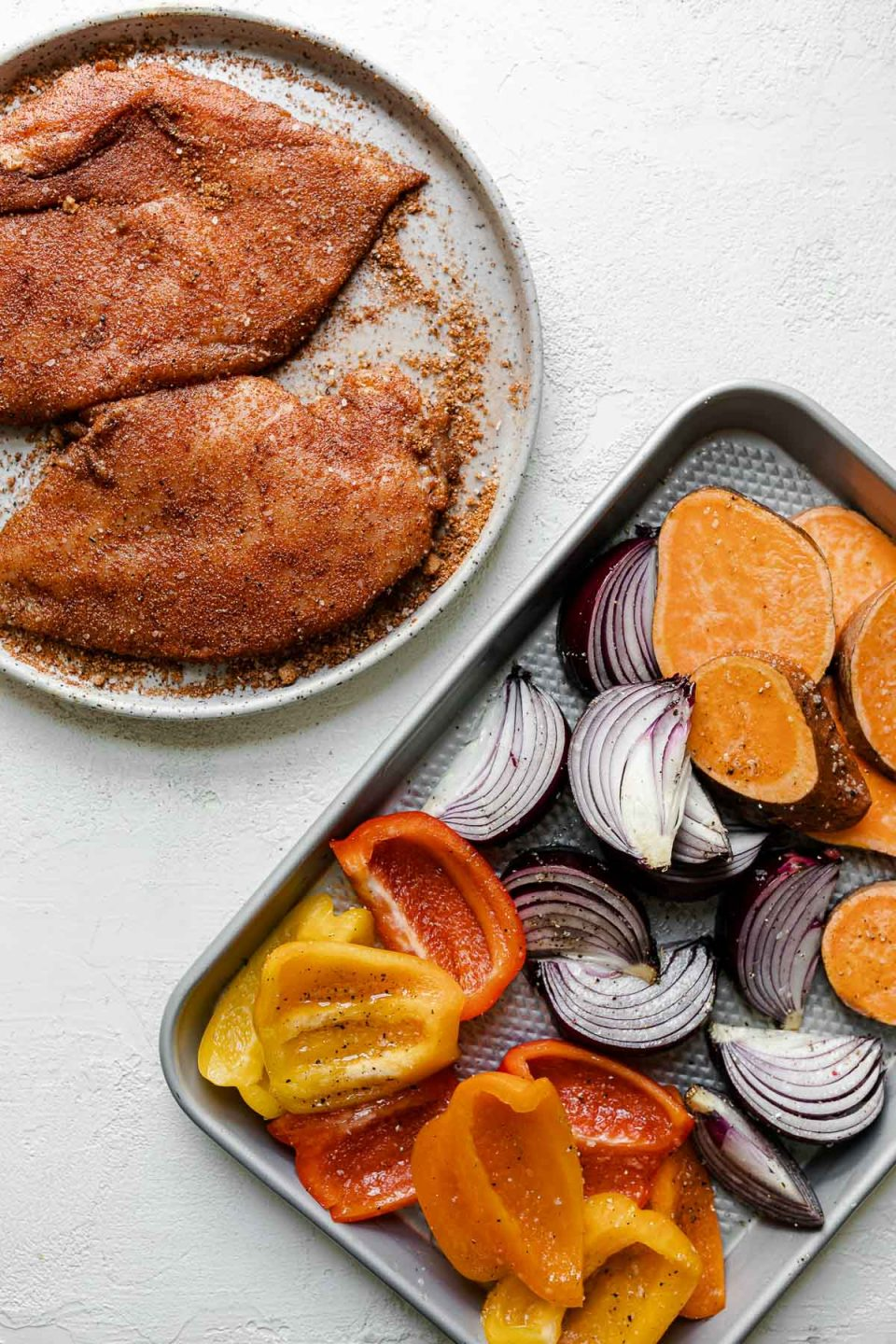 BBQ dry rub-dusted chicken breasts & seasoned sweet potatoes, onions, & bell peppers on a quarter sheet pan atop a white surface.