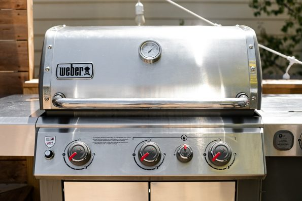 Weber Genesis II grill on a deck, preheated to medium high heat for grilling BBQ chicken & veggies.