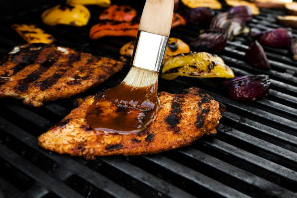 How to make BBQ Chicken Bowls, Step 4: Basting grilled BBQ chicken breasts with BBQ sauce on the grill.