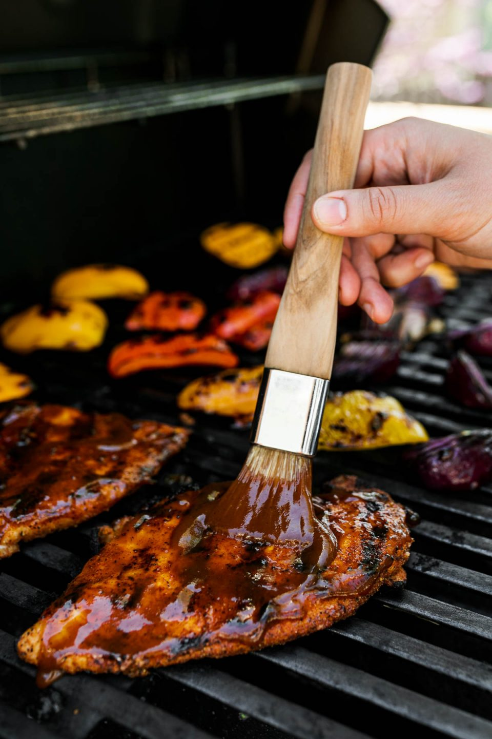 A woman's hand shown using a pastry brush to baste grilled BBQ chicken breasts with BBQ sauce on the grill.