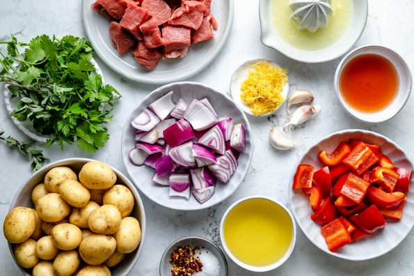 Grilled Steak Kabobs ingredients arranged on a light blue surface: diced top sirloin, red onions, bell pepper & baby potatoes. Chimichurri ingredients alongside them - fresh herbs, lemon zest & juice, olive oil & garlic.