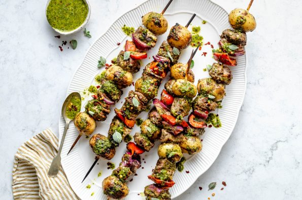 Grilled steak kabobs on a large white oval serving dish, drizzled with chimichurri sauce. The dish sits atop a light blue marbled surface, alongside a small dish of chimichurri sauce & a gold & white striped linen napkin.