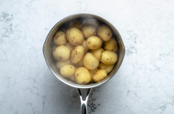 How to make steak and potato kabobs, Step 1: baby potatoes parboiling in a small saucepan, which sits atop a light blue marbled surface.