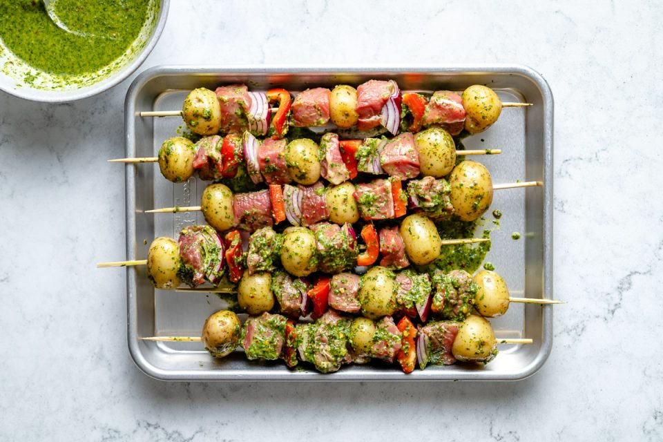 Assembled chimichurri steak kabobs on a small baking sheet atop a light blue marbled surface next to a bowl of chimichurri sauce.