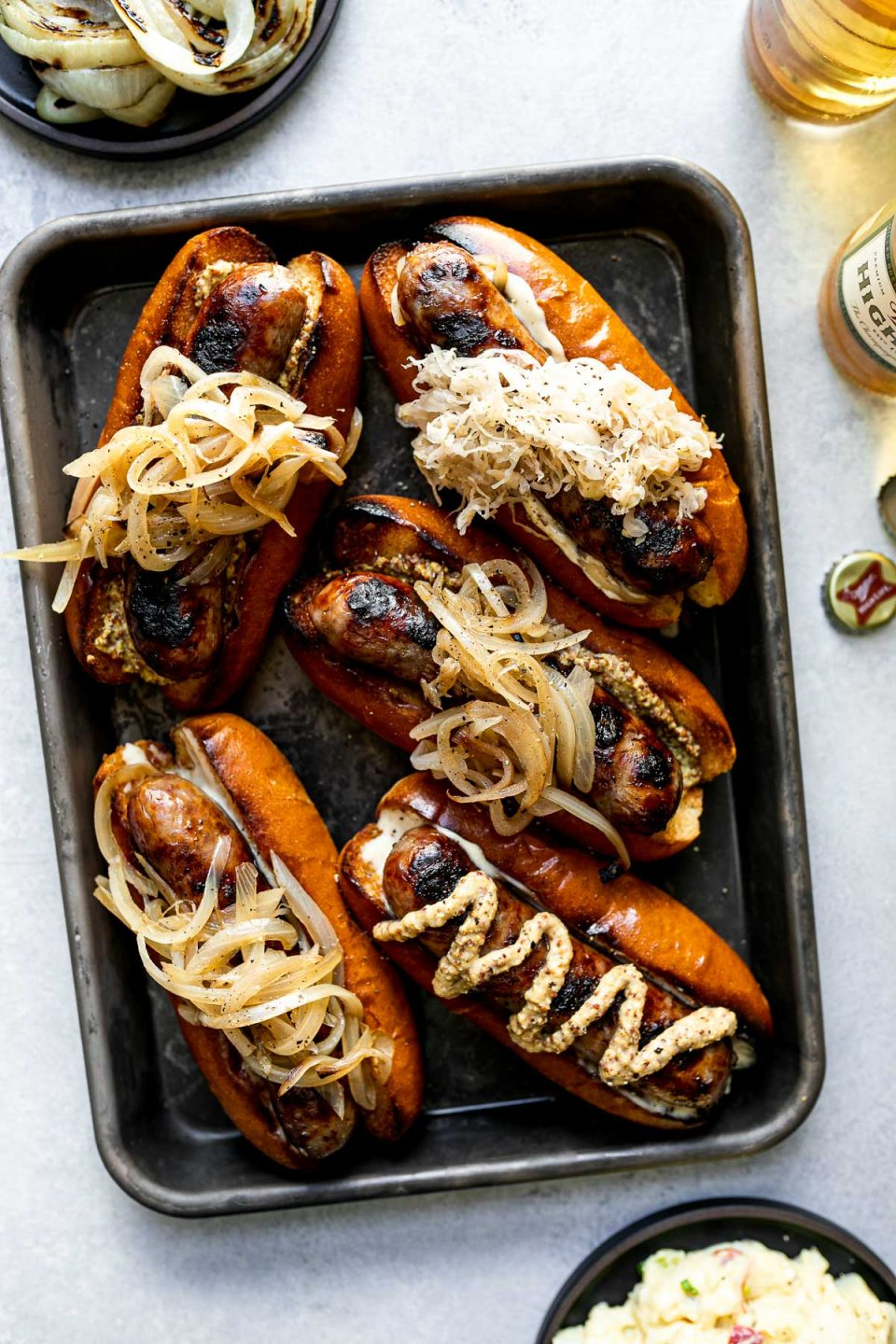Grilled Wisconsin Beer Brats arranged on a small Nordicware baking sheet. The brats sit on toasted brioche buns, topped with mayonnaise, mustard, braised onions, sauerkraut, etc. The baking sheet sits atop a light blue surface, next to some Miller High Life bottle caps & beer bottles, a small black plate of grilled onions, & a small black plate of potato salad.