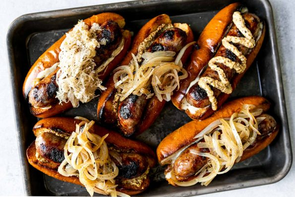 Grilled Wisconsin Beer Brats arranged on a small Nordicware baking sheet. The brats sit on toasted brioche buns, topped with mayonnaise, mustard, braised onions, sauerkraut, etc. The baking sheet sits atop a light blue surface.