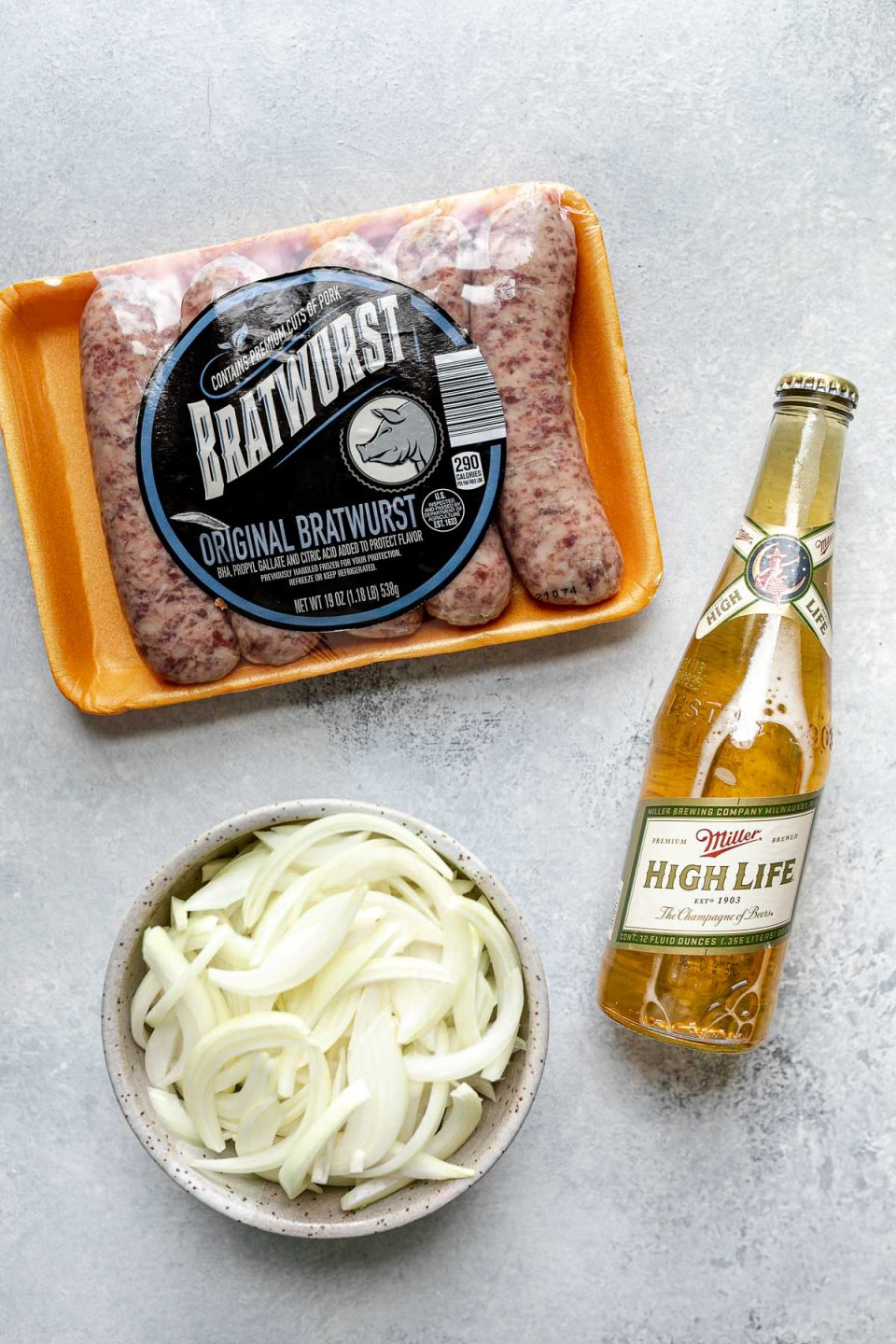 Grilled beer brats ingredients arranged on a light blue surface: Bratwurst from ALDI, Miller High Life, & a bowl of thinly sliced onion.