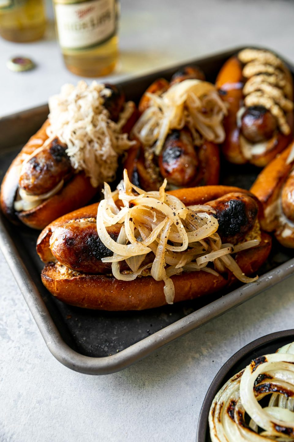 Grilled Wisconsin Beer Brats arranged on a small Nordicware baking sheet. The brats sit on toasted brioche buns, topped with mayonnaise, mustard, braised onions, sauerkraut, etc. The baking sheet sits atop a light blue surface. In the foreground, a small black plate of grilled onions. In the background, 2 bottles of Miller High Life beer.