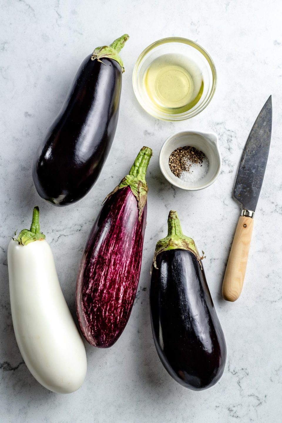 Grilled eggplant ingredients arranged on a white & grey marble surface - whole eggplant in a variety of colors, avocado oil, kosher salt, & ground black pepper. A pairing knife rests on the surface next to the ingredients.