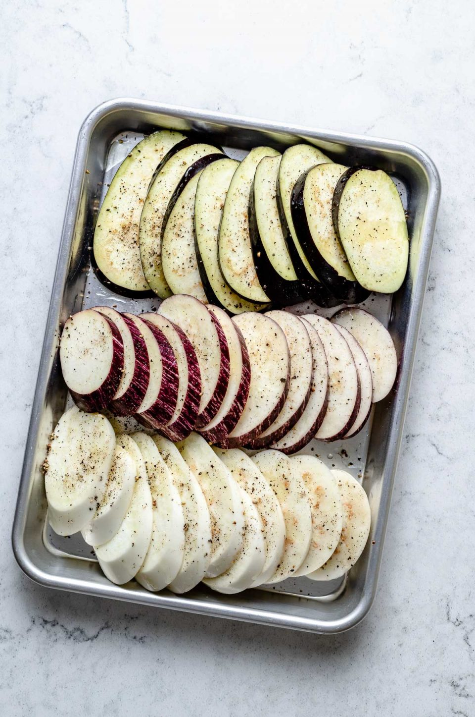 Fresh & raw eggplant sliced in rounds seasoned with avocado oil, kosher salt, & ground black pepper arranged on an aluminum baking sheet. The baking sheet sits on top of a white & gray marble surface.