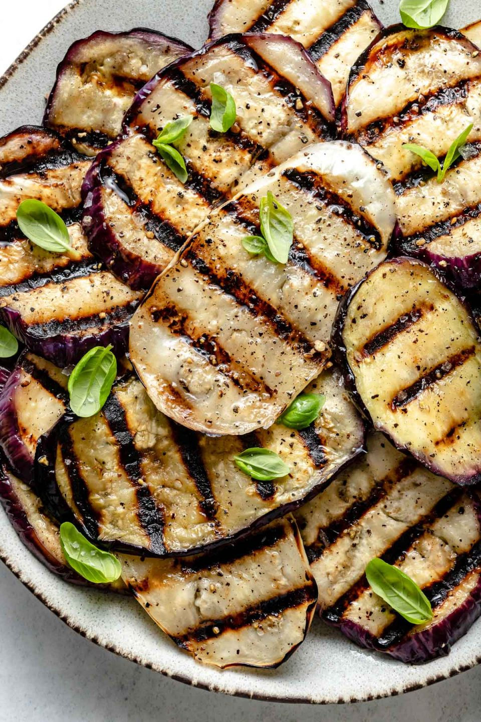 A close up of grilled eggplant rounds with char marks arranged on a white ceramic platter with brown edges. The grilled eggplant is garnished with kosher salt, ground black pepper, & fresh herbs. The platter sits on top of a white & gray marble surface.