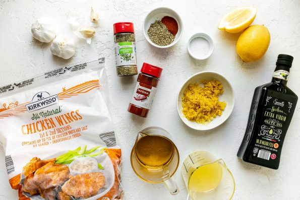 Lemony Greek Grilled Chicken Wings ingredients arranged on a white textured surface – Kirkwood All Natural Chicken Wings from ALDI, kosher salt, Specially Selected Sicilian Extra Virgin Olive Oil from ALDI, lemon zest, lemon juice, garlic, Stonemill Dried Oregano & Paprika from ALDI.