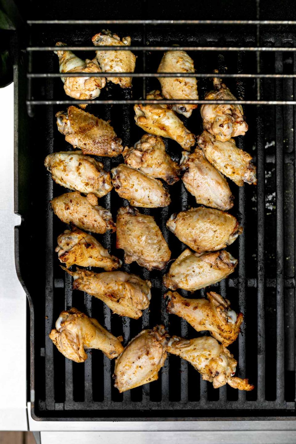 Grilled Lemony Greek Chicken Wings sit on top of Weber Grill grates.