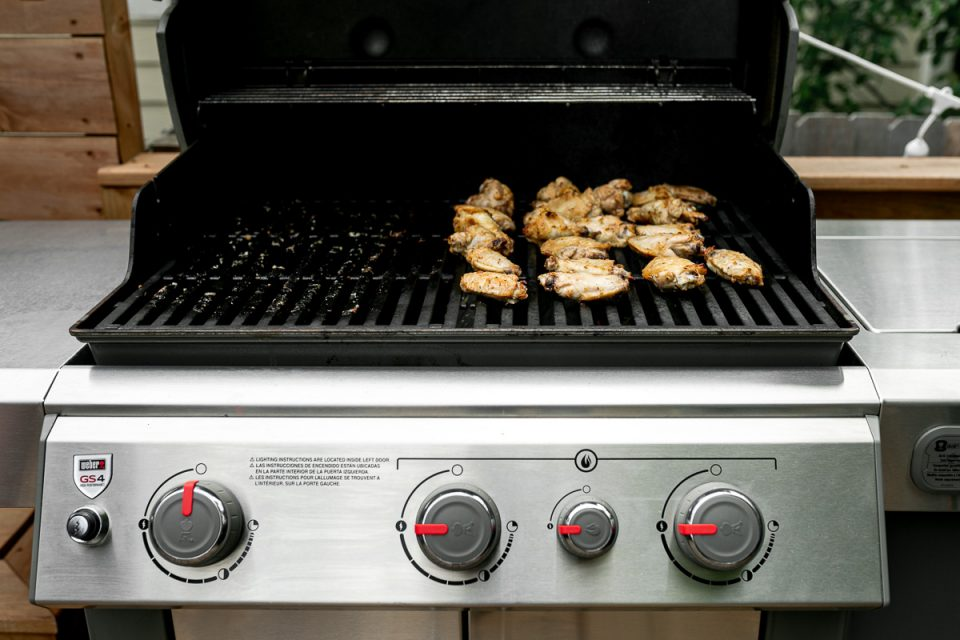 Grilled Lemony Greek Chicken Wings sit on top of Weber Grill grates over direct heat. The grill burners are set to high heat to help the wings develop crispy char marks & flavor.