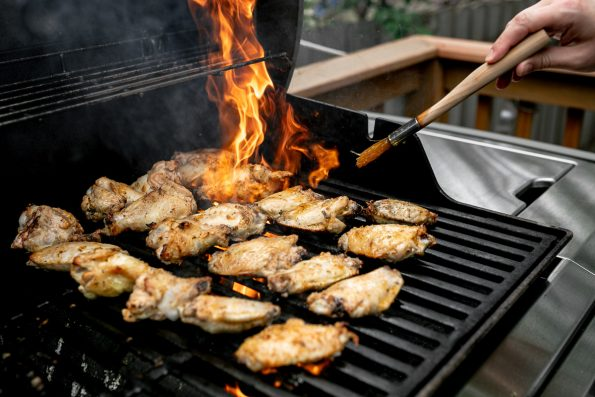 Grilled Greek Chicken Wings being char-grilled on a Weber Grill over direct heat. Flames from the grill burners are present as the chicken wings finish on the grill. A woman's hand holds a pastry brush & brushes on reserved lemony greek marinade over the grilled wings.