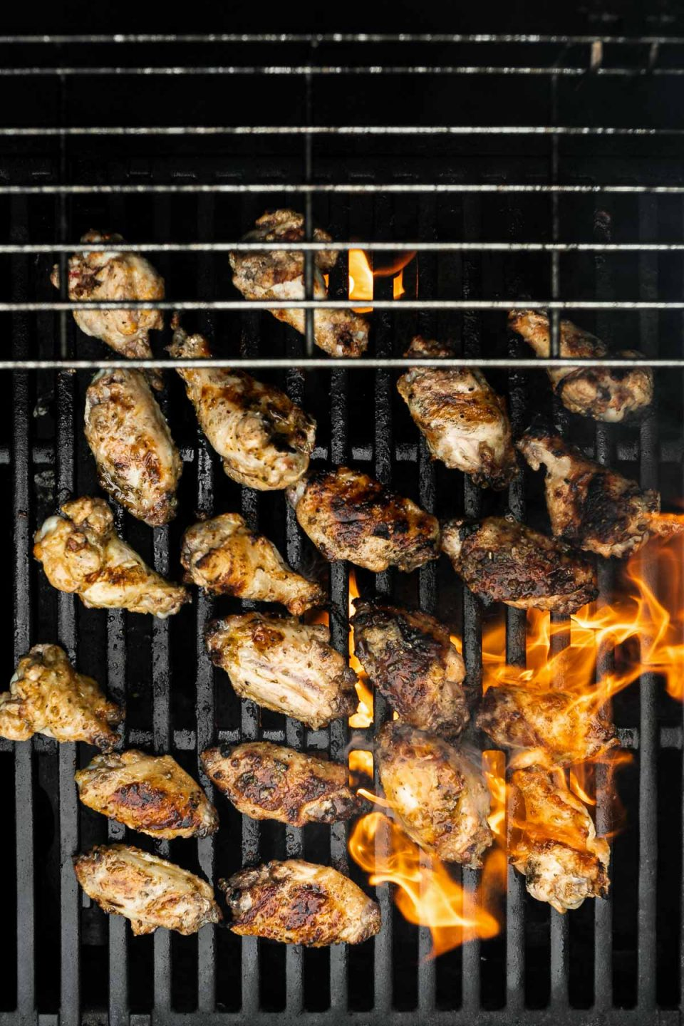 Grilled Greek Chicken Wings being char-grilled on a Weber Grill over direct heat. Flames from the grill burners are present as the chicken wings finish on the grill.