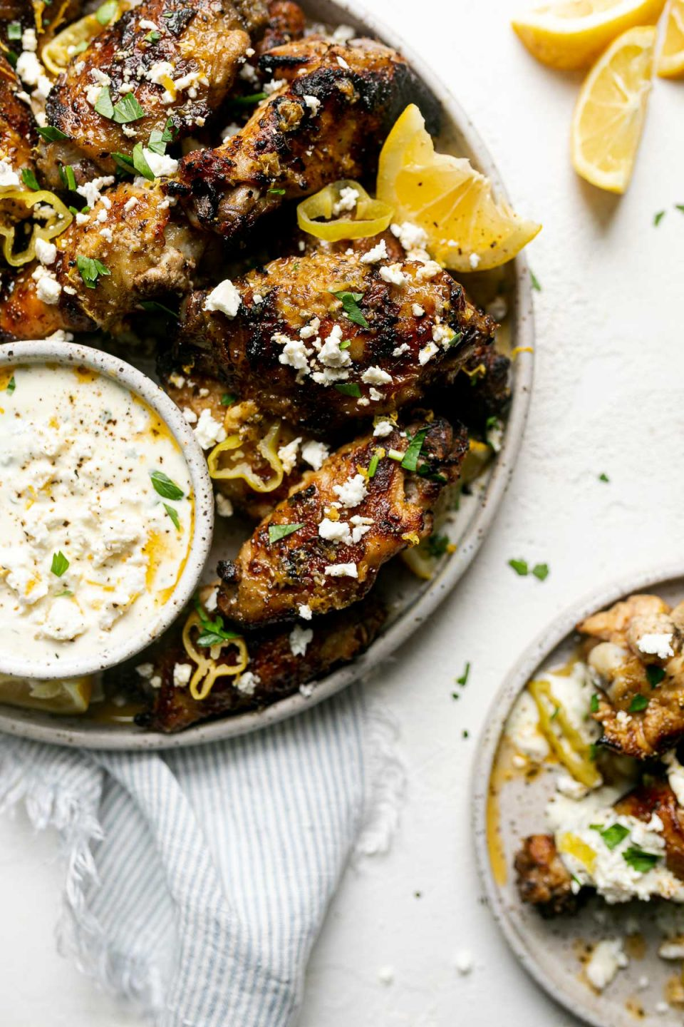 Grilled Greek Chicken Wings arranged on a gray speckled ceramic platter are garnished with herbs, sliced pepperocini, lemon wedges, & feta cheese. A small ceramic bowl is filled with whipped feta dip & also sits on the platter with wings surrounding it. Surrounding the plate is a small plate of wings, a bowl of whole pepperocini peppers, lemon wedges, feta crumbles, loose chopped herbs, & a blue & white striped linen napkin tucked partially under the platter. The platter & surrounding items sit on top of a white textured surface.