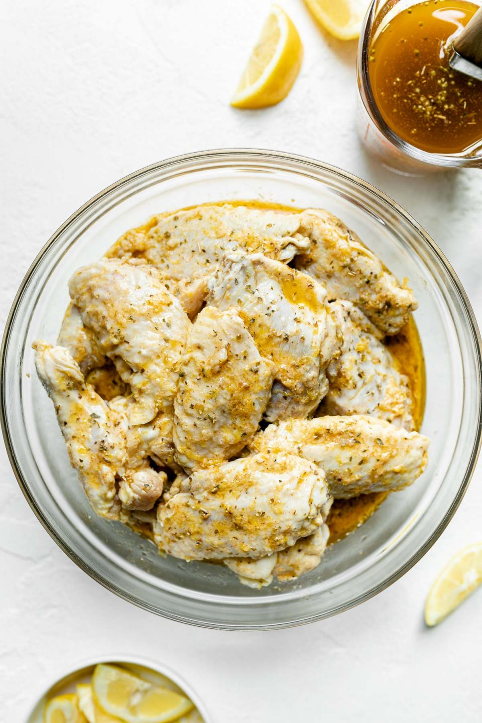 Chicken Wings rest in a bowl of Lemony Greek marinade with a glass measuring cup of reserved marinade to the side. A pastry brush sits inside the glass measuring cup, & cut lemon wedges sit loose & in a small dish surrounding the glass bowl of marinating chicken wings. All items sit on top of a white textured surface.