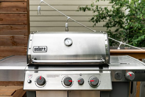 A shot of a Weber Genesis II Grill prepped for grilling Lemony Grilled Greek Chicken wings. The grill burners are set such that the left side of the grill is ready for indirect heat grilling, while the right side of the grill is ready for direct heat. The grill sits on top of a wooden deck. In the background there is a tree, white cafe lights strung, & beige siding shown of a house behind the grill.
