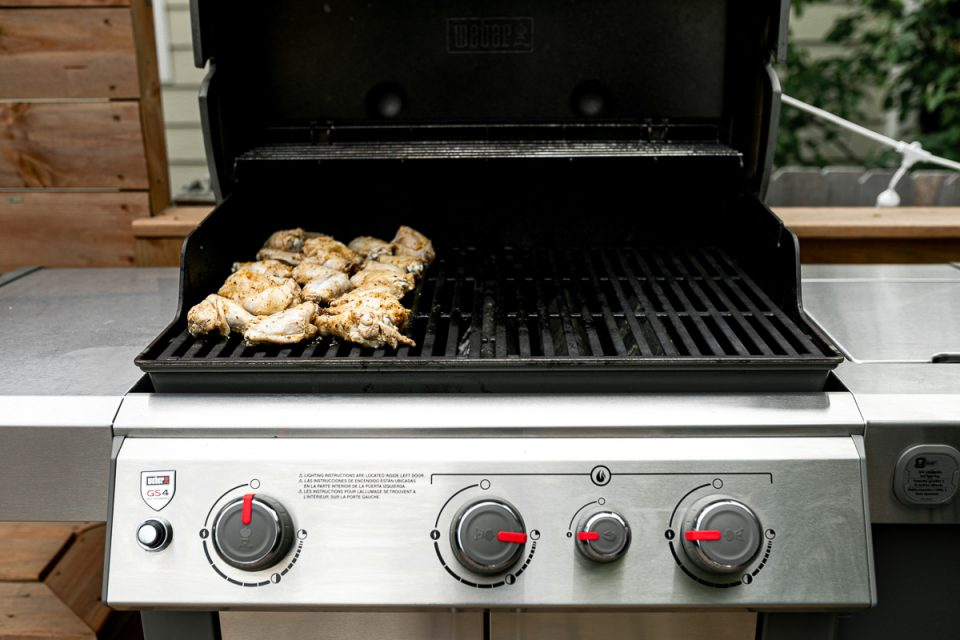 Grilled Lemony Greek Chicken Wings sit on top of Weber Grill grates over indirect heat. The far left grill burner, that the chicken wings sit over is off, while the grill burners to the right are partially turned on to achieve optimum temperature for indirect grilling of the chicken wings.